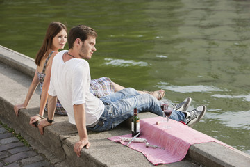 Couple sitting at the ledge of a canal, Paris, Ile-de-France, France