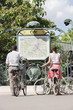 Couple with bicycles looking at a map, Paris, Ile-de-France, France