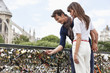 Couple locking a padlock of love on a bridge, Pont des Arts, Notre Dame de Paris, Paris, Ile-de-France, France