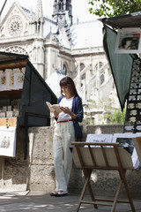 Woman reading a book at a book stall, Notre Dame de Paris, Paris, Ile-de-France, France