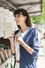 Woman pointing at a book at a book stall, Paris, Ile-de-France, France