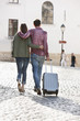 Rear view of a couple walking on a road with a suitcase, Paris, Ile-de-France, France