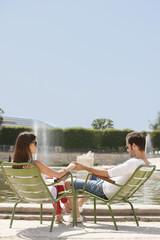 Couple sitting in chairs near a pond, Bassin octogonal, Jardin des Tuileries, Paris, Ile-de-France, France