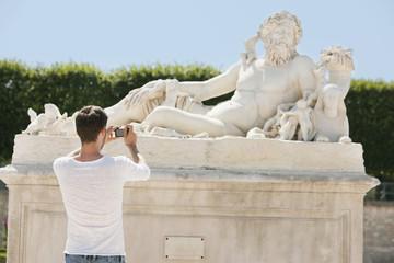 Man taking a picture of a sculpture in a garden, Jardin des Tuileries, Paris, Ile-de-France, France