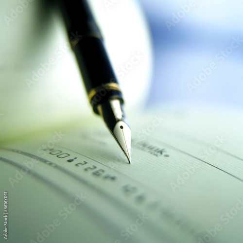Person writing check with pen and checkbook