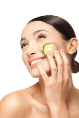 face of beautiful woman with cucumber slices around the cheeks