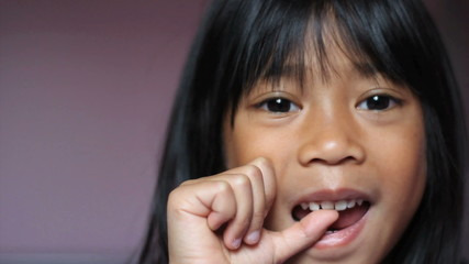 Asian Girl Wiggling Her First Loose Tooth-Close Up