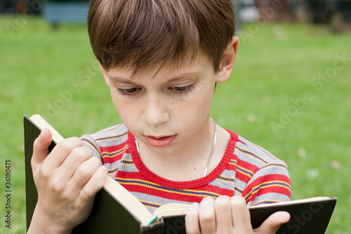 cute boy reading a book in a park