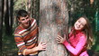 Young couple hiding behind tree trunk and smiling