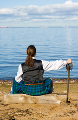 Man in scottish costume looking at the sea