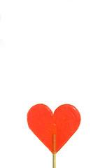 Ein Lolli in Herzform vor weißem Hintergrund