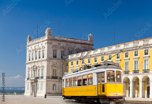 Leinwandbild Motiv Lisbon yellow tram at central square Praca de Comercio, Portugal