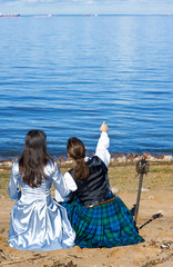 Woman and man in scottish costume sitting near the sea