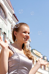 Beautiful girl with soap bubbles against a background of sky