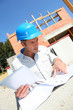 Entrepreneur checking plan on construction site