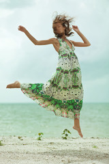Girl jumping on beach, feels free