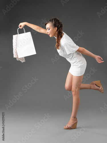 fashionable young woman holding shoppping bag, tumbling