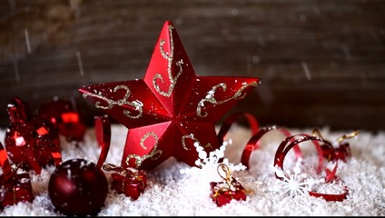 snow falling on red star and christmas ball ornaments