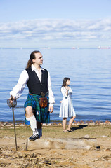 Man in scottish costume and woman near the sea