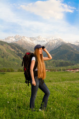 Happy woman with backpack standing on a mountain