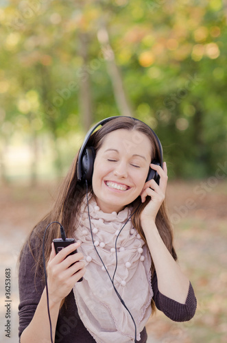 Happy young lady listening music on mobile phone