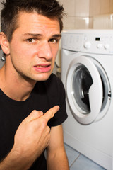 Young man unhappy with washing mashine