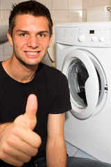 Young man happy with washing mashine