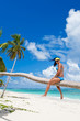Tanned woman sitting on a palm white sand beach