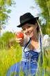 Frau mit Hut in der Wiese zeigt Apfel
