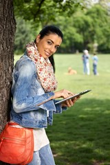 Attractive woman using tablet in park smiling