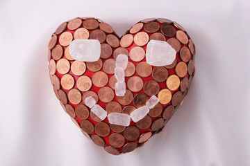 A smiling red heart with 1 Euro cent coins