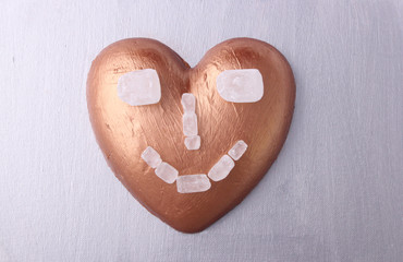 A smiling copper heart on silver background