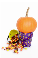 Pumpkin with candy falling out of Halloween buckets