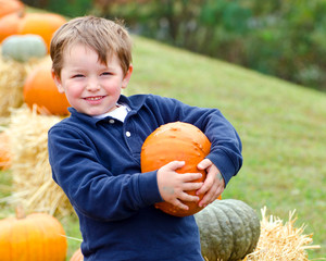 Happy young boy picking a pumpkin for Halloween