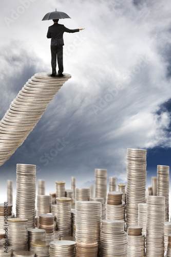 businessman stand on the coins  watching the storm