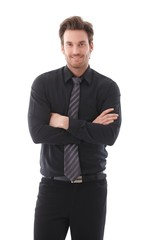 Young businessman smiling arms crossed