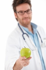 Young doctor offering green apple