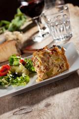 Stück Quiche Lorraine mit Salat und Wein