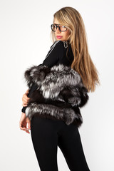 A woman in dark glasses and a fur coat.