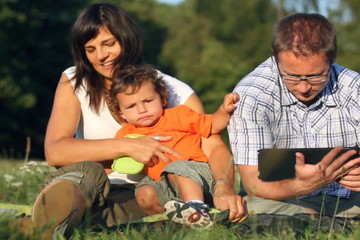 Happy family with tablet computer in the park, dolly shot
