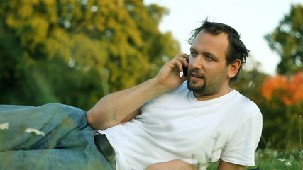 Man lying in the park and talking on mobile phone