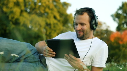 Young man with headphones and tablet computer in the park