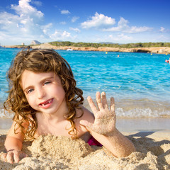 Little girl greeting hand gesture in sandy beach