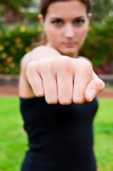 Chica de negro apuntando con el puño