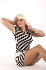 sitzende, blonde Frau in modischer Kleidung