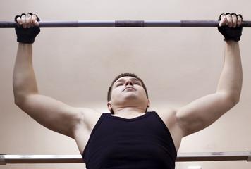 Close-up of man lifting  metal weight