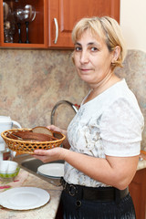 Mature woman standing in kitchen with plate of bread