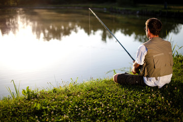 Man fishing in a pond. Back view. Shallow DOF.