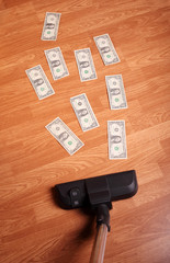 Vacuum cleaner on floor with money notes