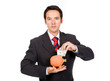 Businessman inserting money into a piggy moneybox, isolated on w